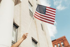 US flag waved from window