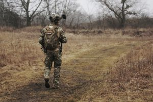man in army suit walking along brown grass