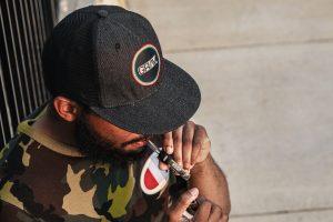 man in black cap smoking joint