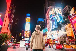 man walking in Times Square NYC at night