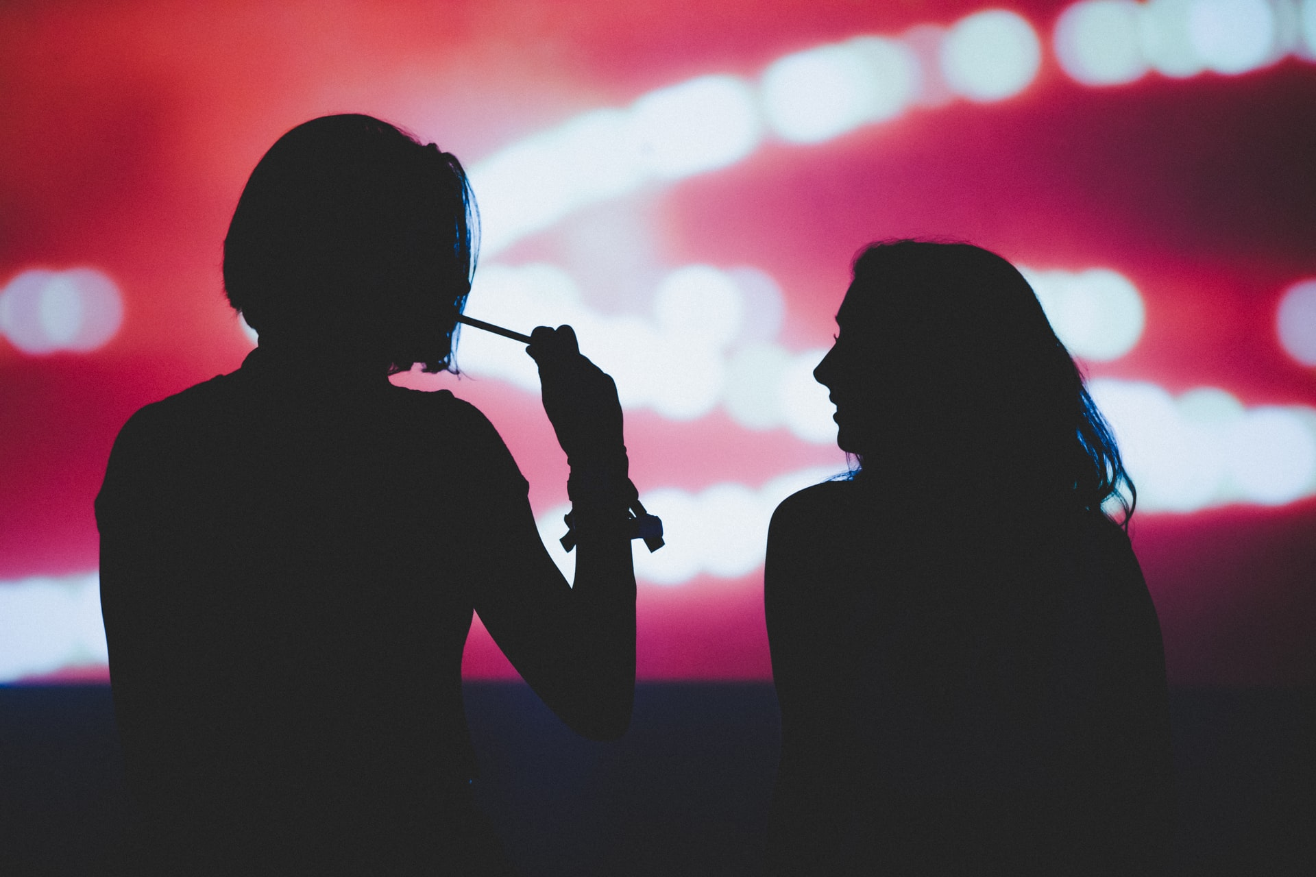 silhouette of two people smoking weed