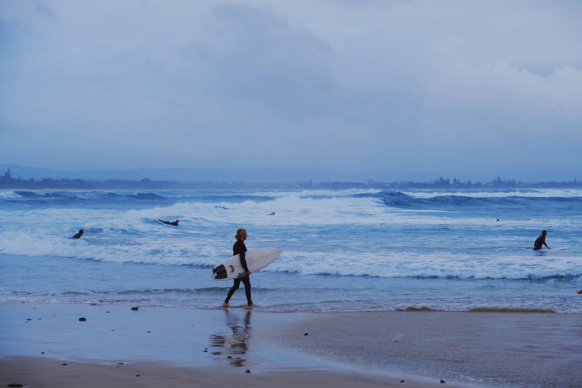 surfer walking to ocean in Byron Bay