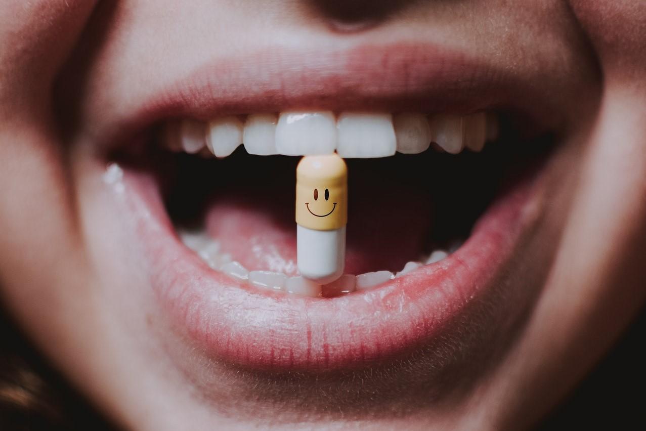 woman holding pill between teeth