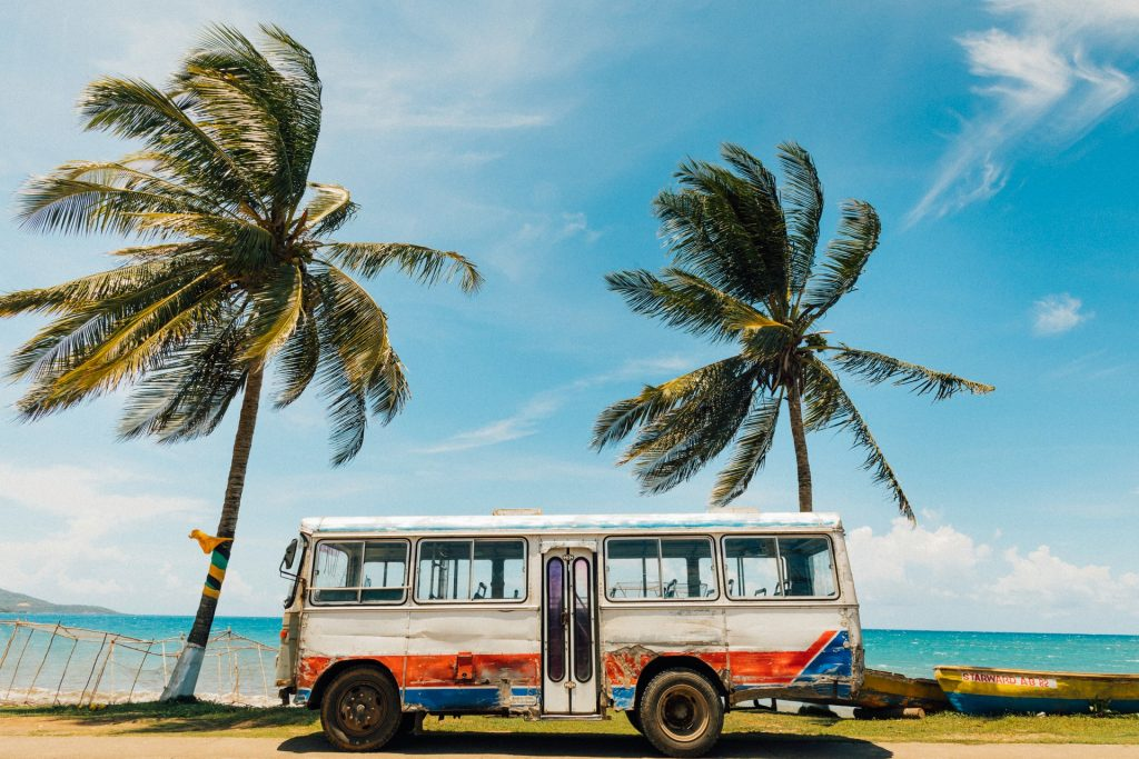 Jamaica - old bus sitting in front of ocean and palm trees