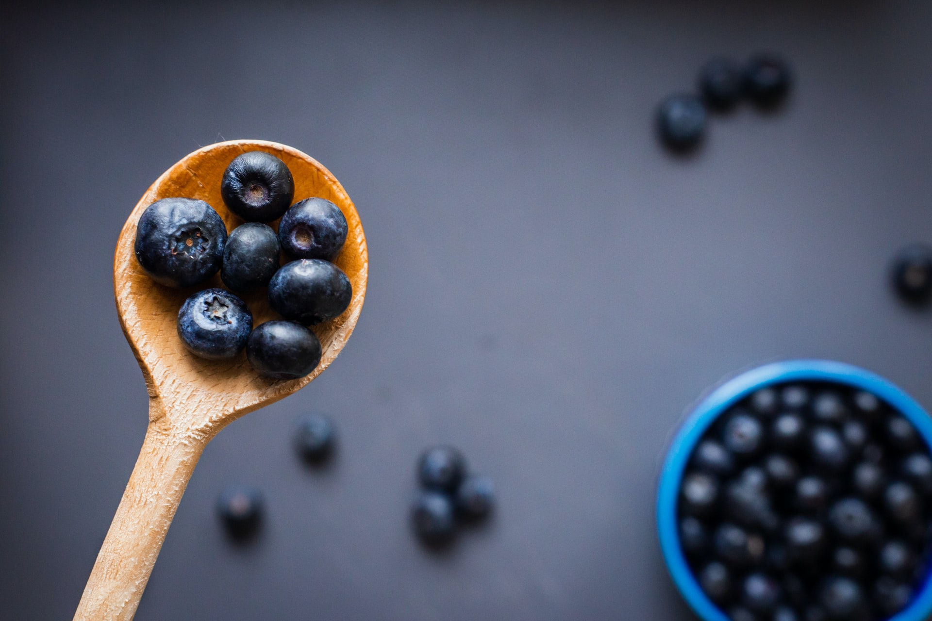 bowl and spoon of blueberries on purple backdrop
