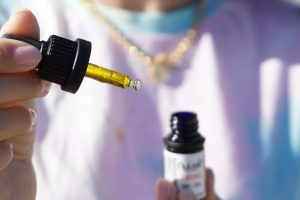 close up of someone holding CBD oil bottle