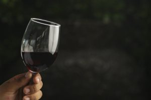 hand holding a glass of red wine with dark background