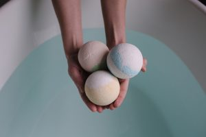 hand holding out three bath bombs