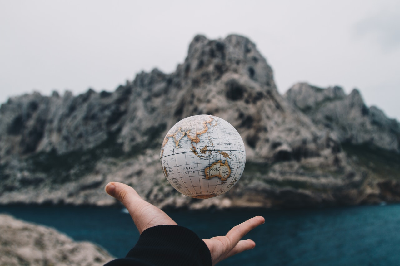 hand throwing small globe in front of mountain