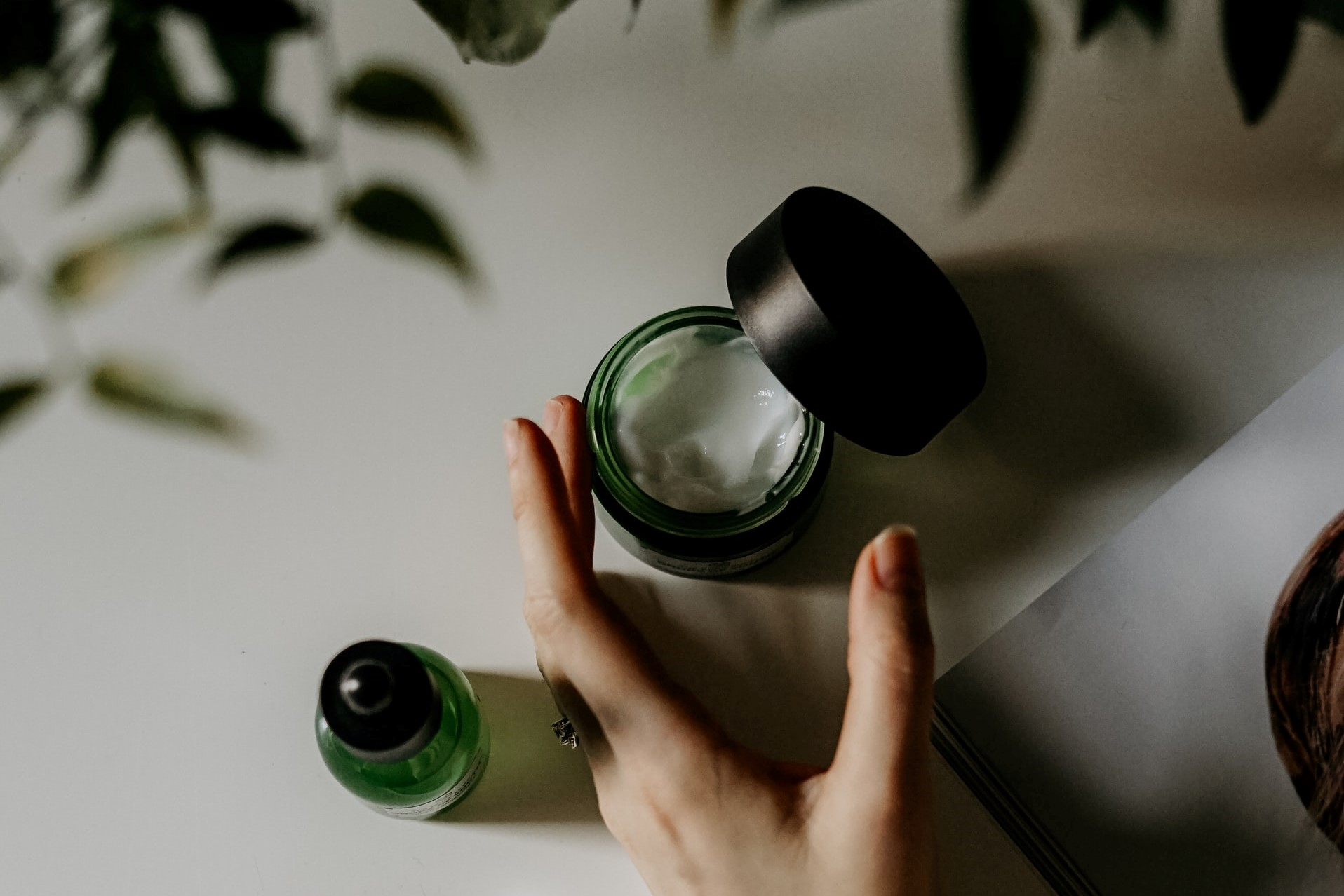 holding a small green bottle of face cream