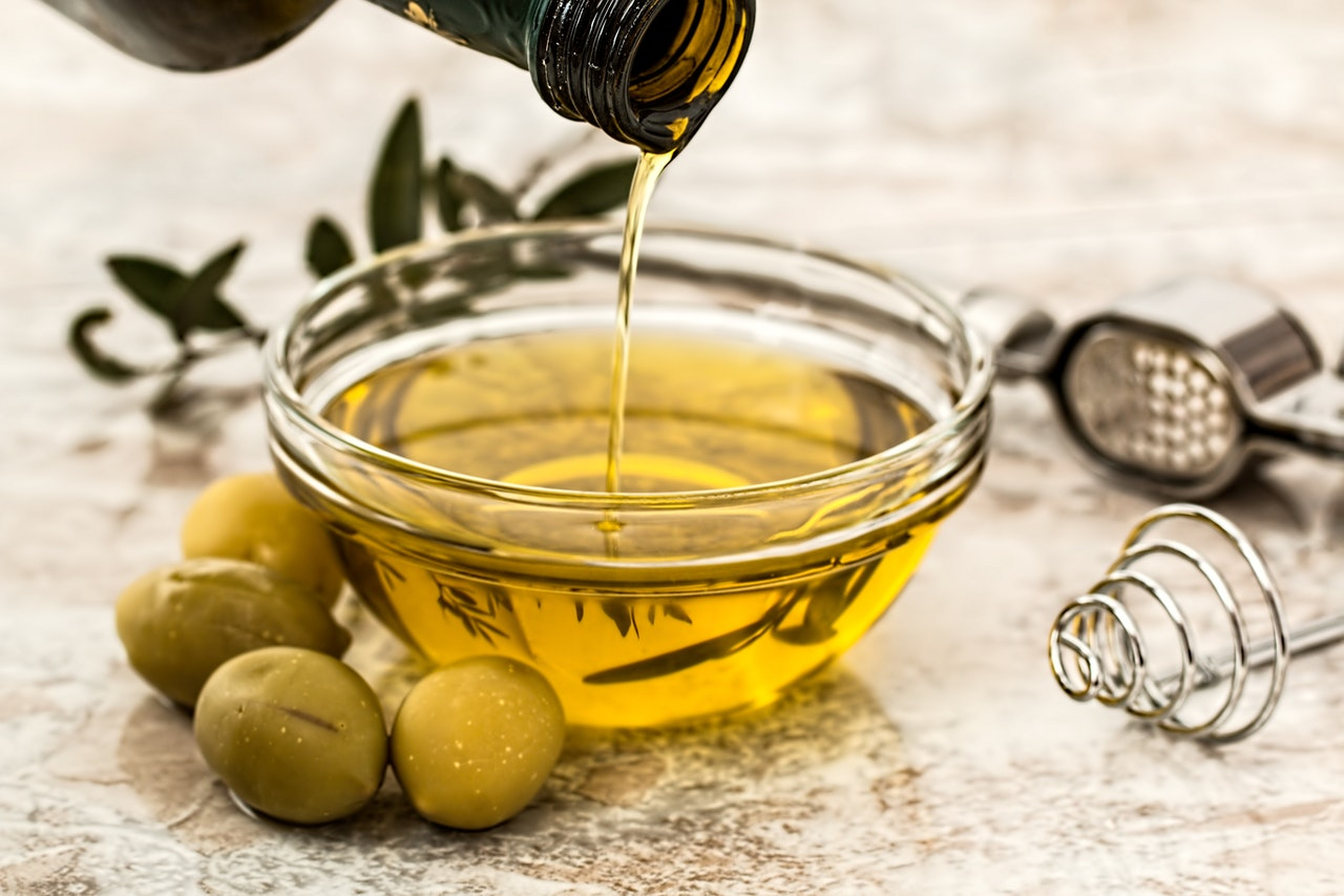 olive oil being poured into small glass bowl