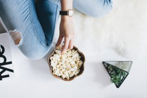 person in jeans eating popcorn from bowl