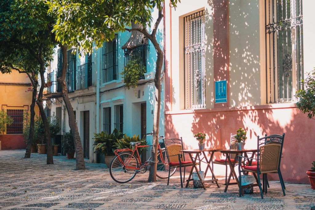 quaint street in Spain with tables, chairs and bicycle