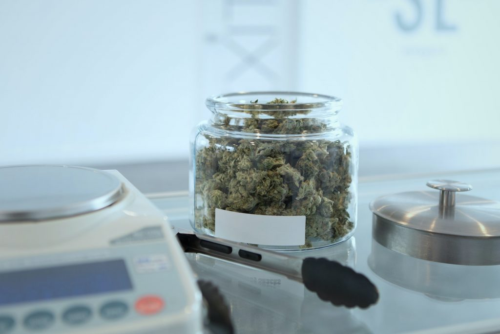 weed in glass jar next to scales