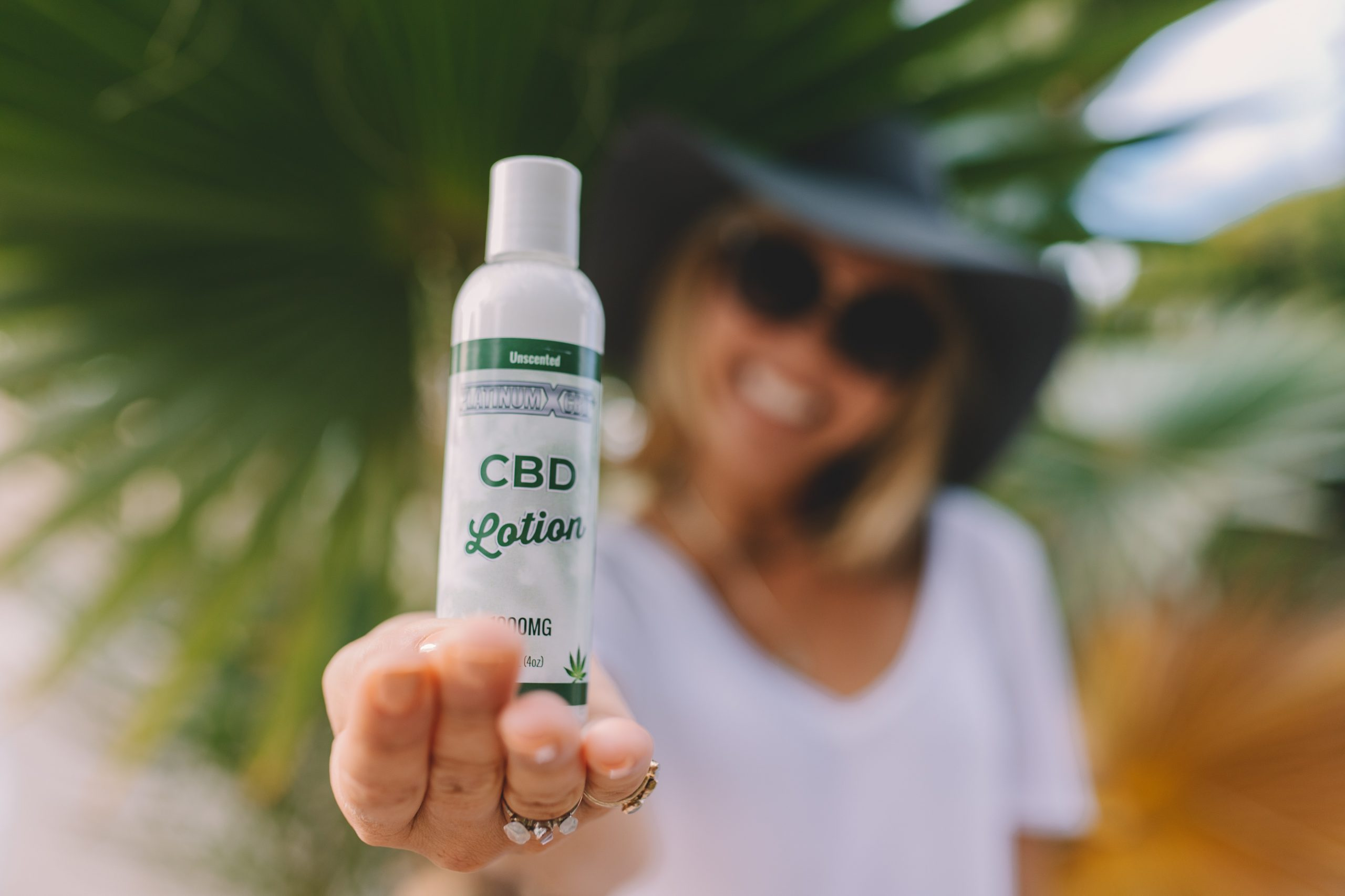 woman in hat holding CBD lotion to camera