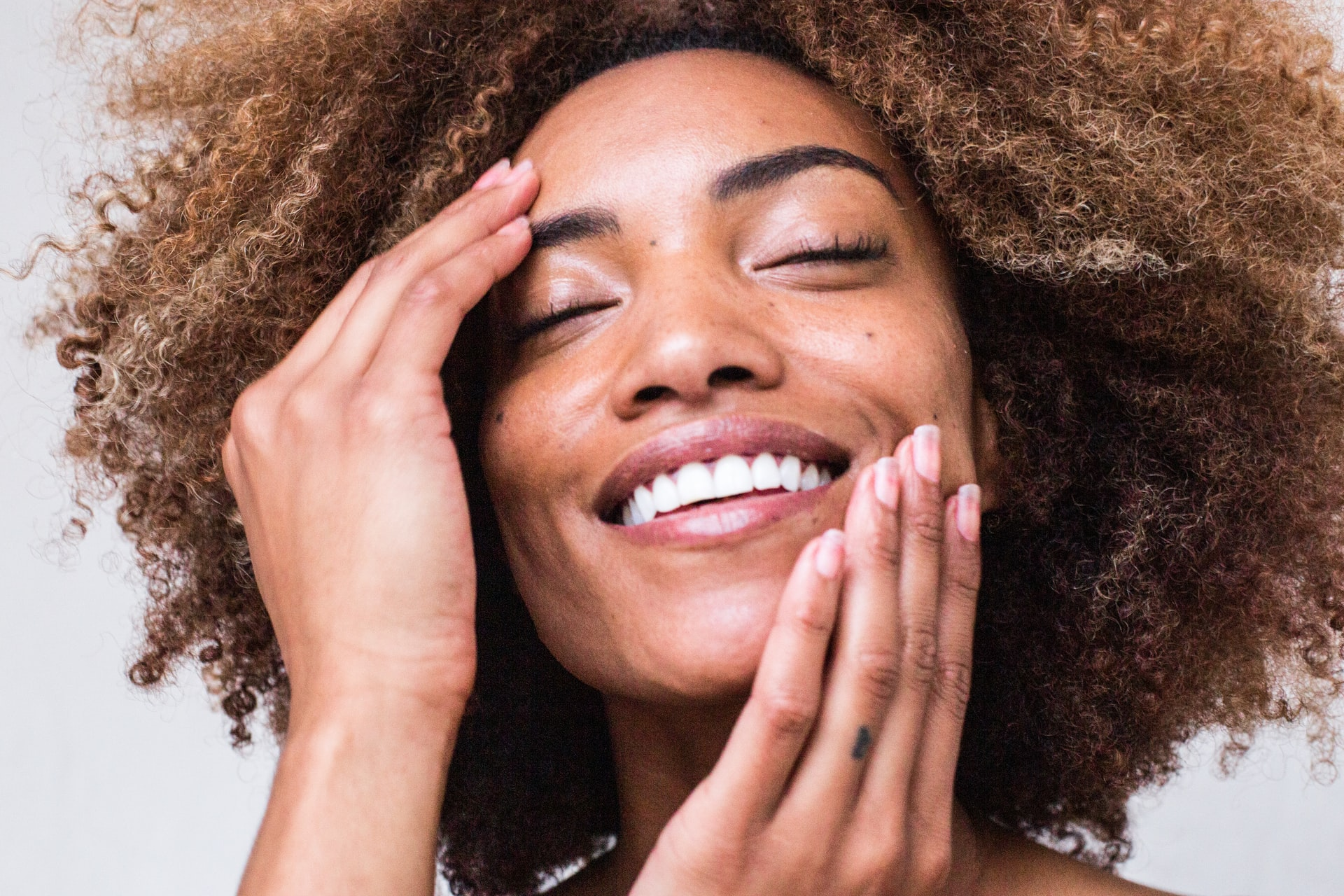 woman with afro smiling and touching face