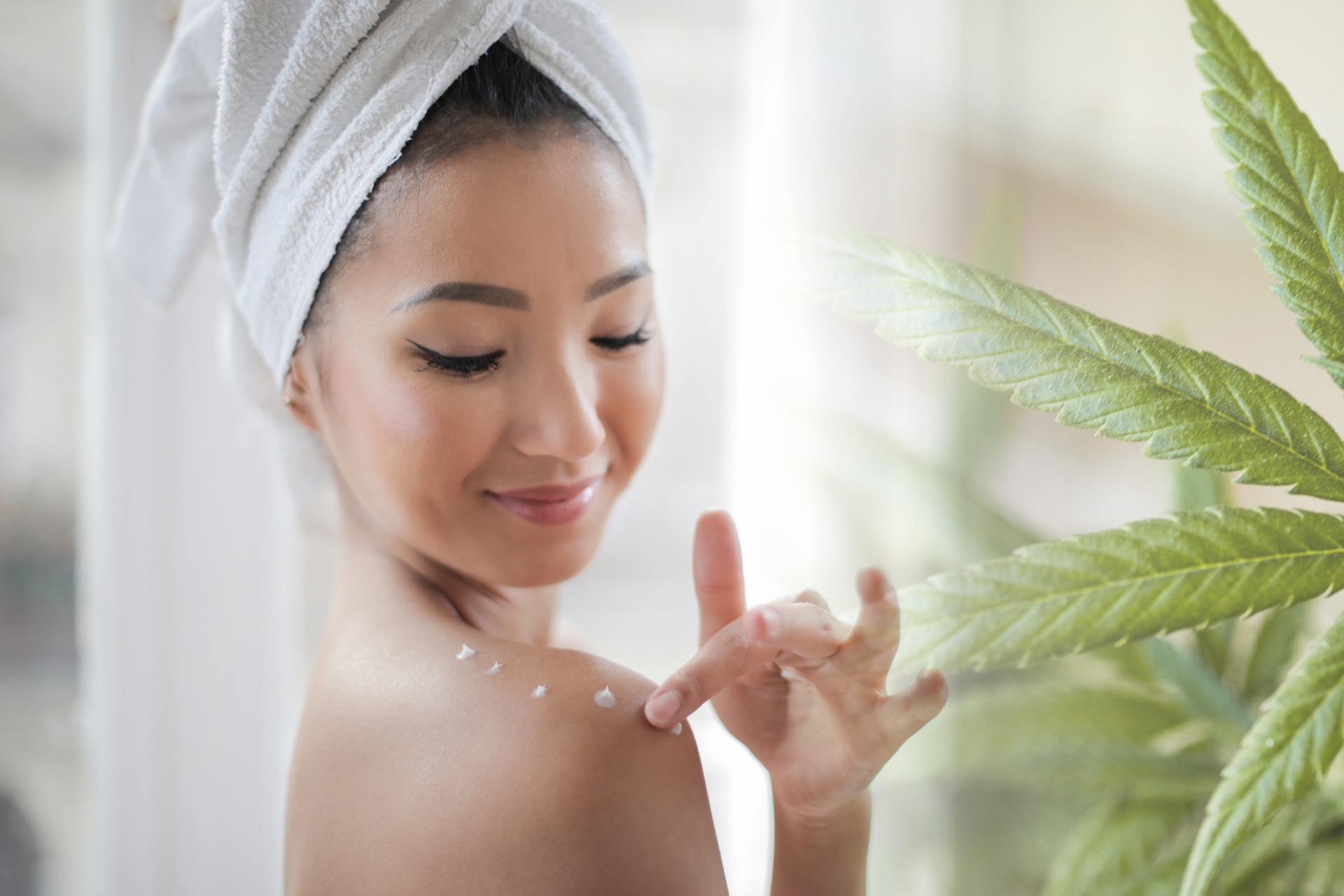woman with towel on head putting on lotion on shoulders